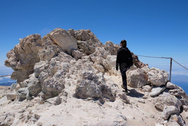 Mulher que ascensão o pico de montanha de Teide em uma paisagem vulcânica seca e rochosa fotografia de stock royalty free