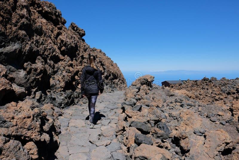 Mulher que ascensão o pico de montanha de Teide em uma paisagem vulcânica seca e rochosa fotos de stock