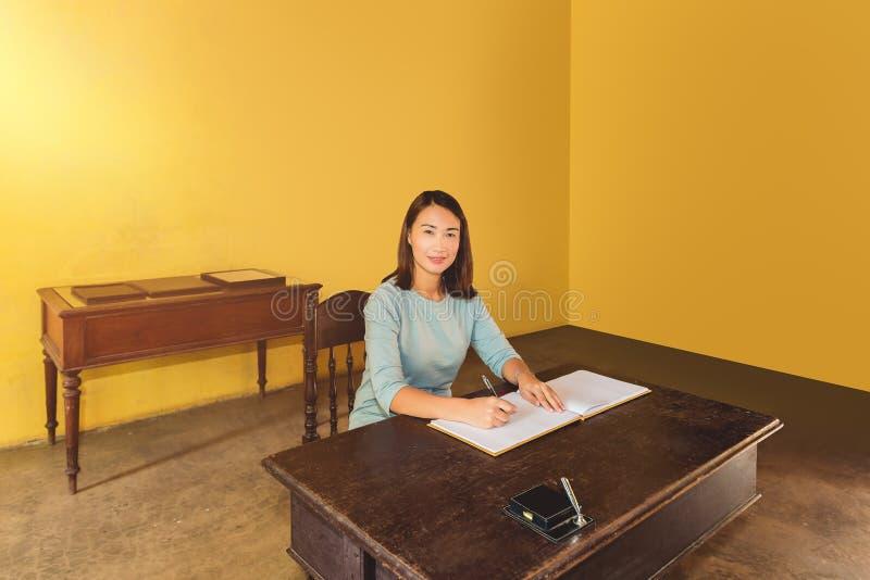 Mulher que assina um livro de hóspedes com uma pena imagem de stock