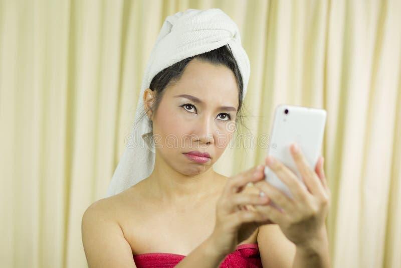 Mulher que atua de jogo no telefone veste uma saia para cobrir seu peito após o cabelo da lavagem, envolvido nas toalhas após o fotografia de stock