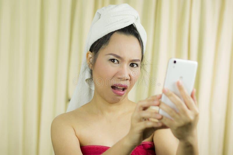 Mulher que atua de jogo no telefone veste uma saia para cobrir seu peito após o cabelo da lavagem, envolvido nas toalhas após o foto de stock royalty free