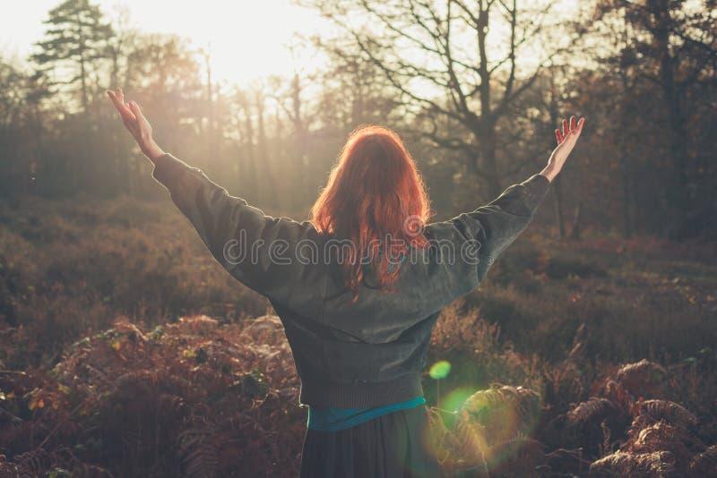 Mulher que aumenta os braços alegremente no por do sol na floresta foto de stock