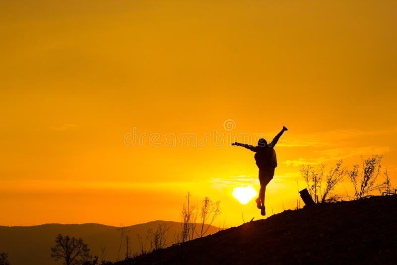 Mulher que backpacking para olhar o por do sol Silhueta, salto contente fotografia de stock