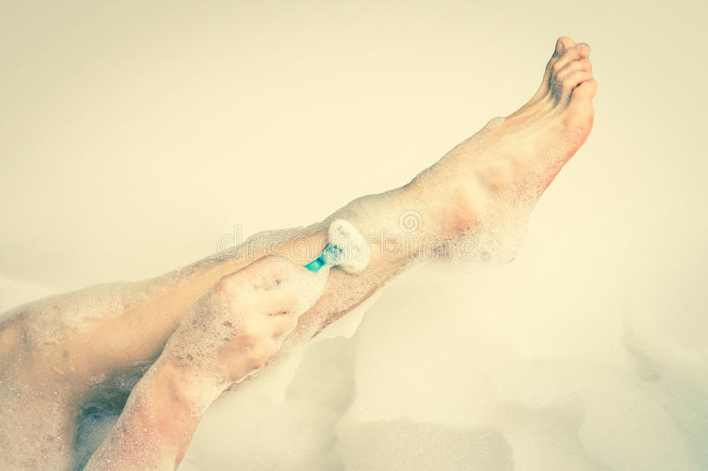 Mulher que barbeia os pés com a lâmina no banheiro - estilo retro imagens de stock