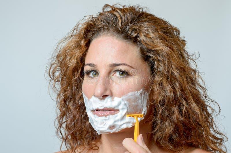 Mulher que barbeia sua barba imagens de stock royalty free