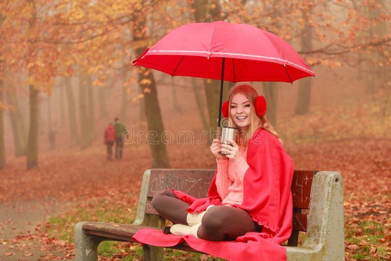 Mulher que bebe o café quente que relaxa no parque do outono fotos de stock