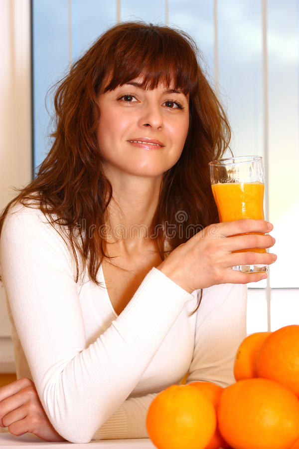 Mulher que bebe o sumo de laranja fresco fotografia de stock