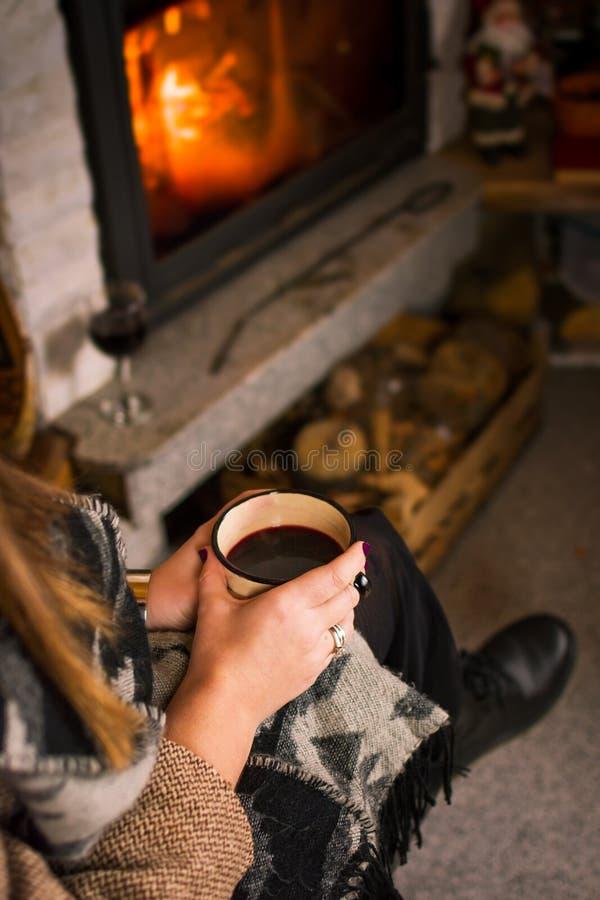 Mulher que bebe o vinho ferventado com especiarias pela chaminé fotos de stock royalty free