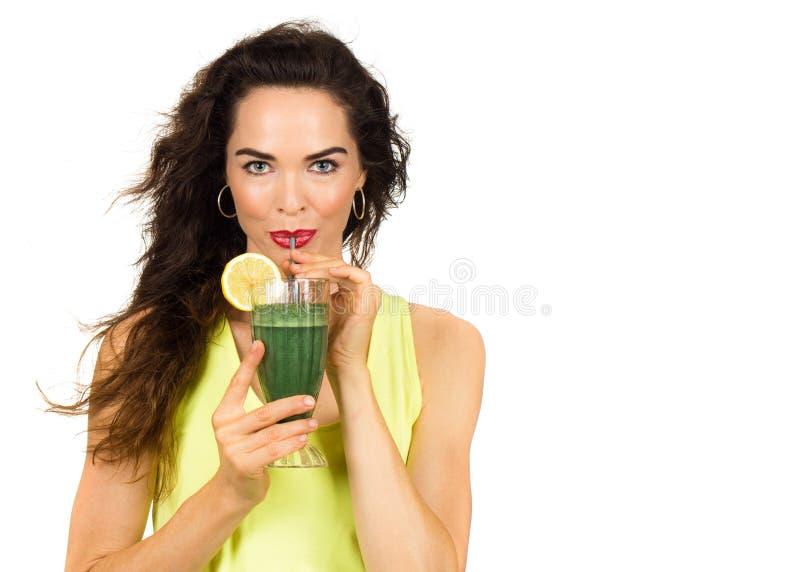 Mulher que bebe um batido verde. imagens de stock