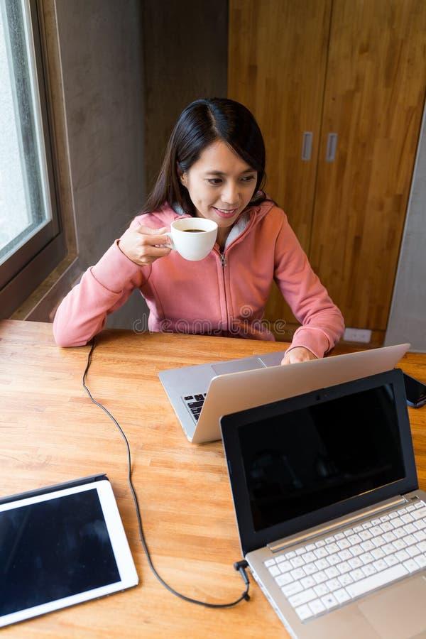 Mulher que bebe um copo do chá e que usa o laptop foto de stock royalty free