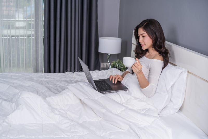 Mulher que bebe uma xícara de café e que usa o laptop na cama fotografia de stock royalty free