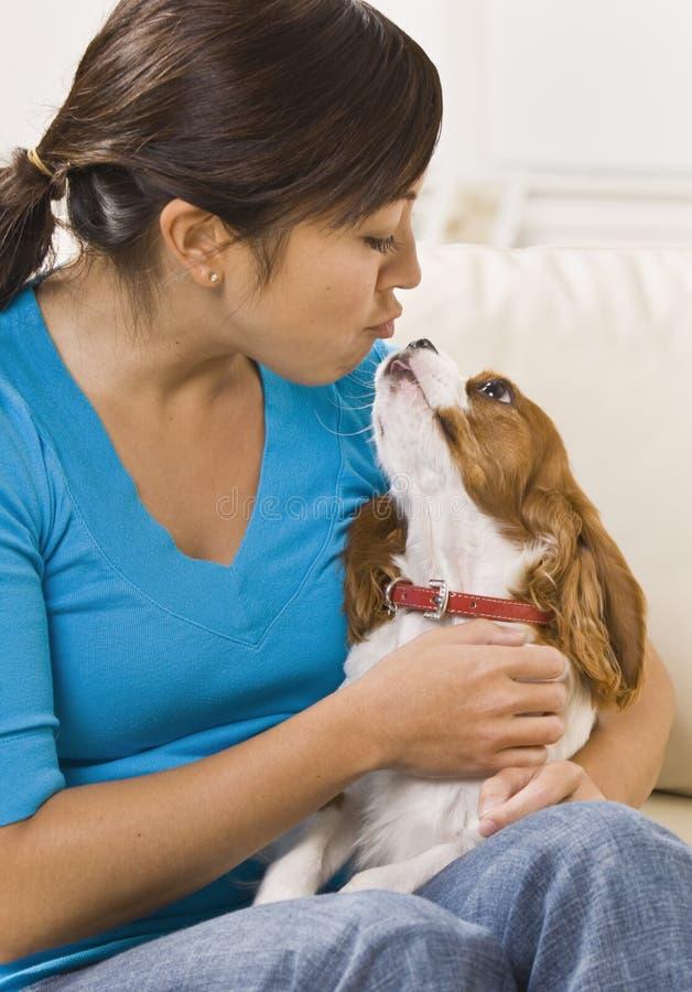 Mulher que beija o cão fotos de stock royalty free