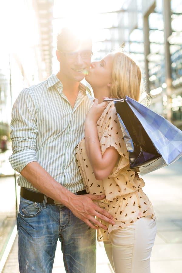 A mulher que beija o homem na compra e está feliz fotografia de stock