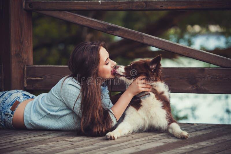 Mulher que beija seu cão imagem de stock