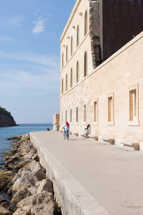 Mulher que Bicycling em Marselha perto da borda do ` s da água imagens de stock