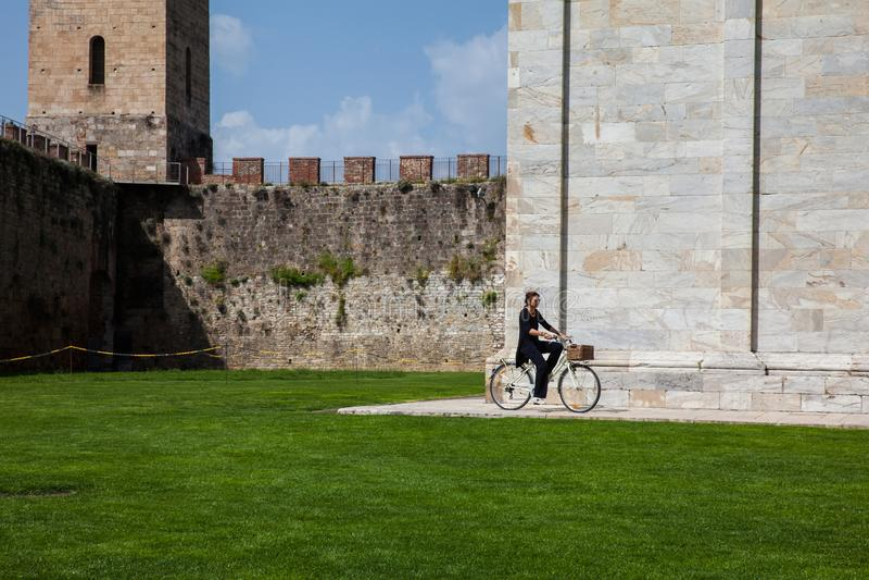 Mulher que biking ao lado das paredes antigas de Pisa e do cemitério monumental no quadrado dos milagre na foto de stock royalty free