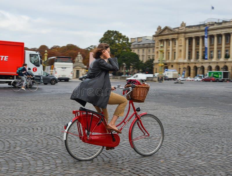 Mulher que biking na rua de Paris, França imagem de stock royalty free