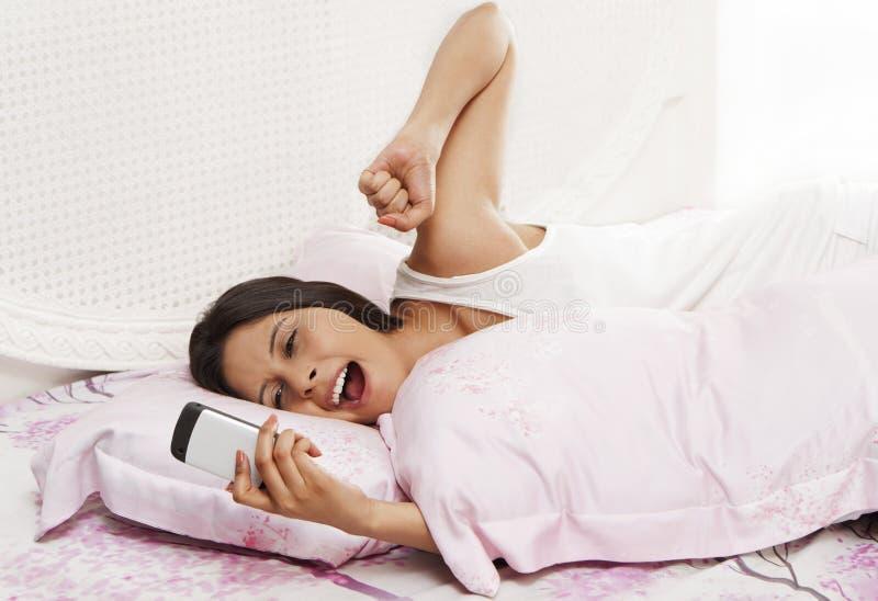 Mulher que boceja na cama e que guarda um telefone celular imagens de stock