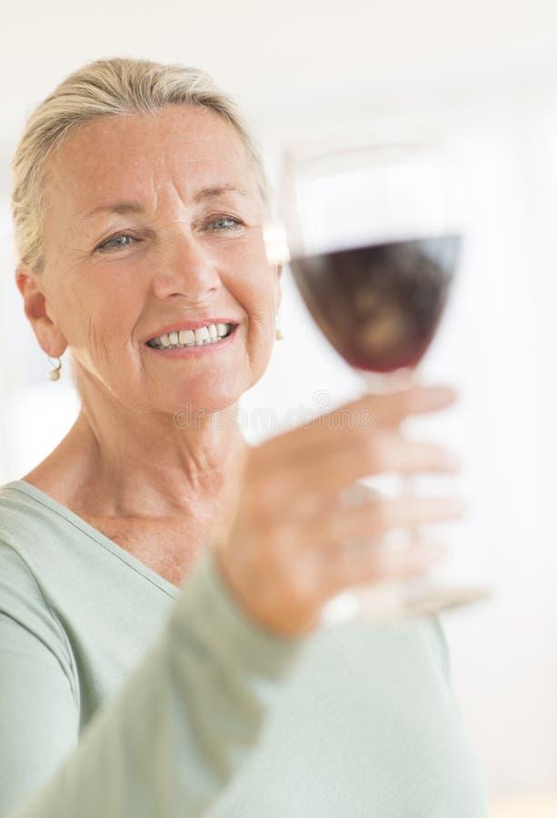 Mulher que brinda o copo de vinho em casa imagens de stock royalty free