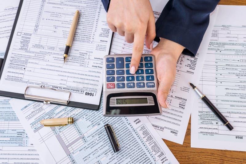 Mulher que calcula seus impostos, formulário de imposto 1040 individual fotografia de stock royalty free