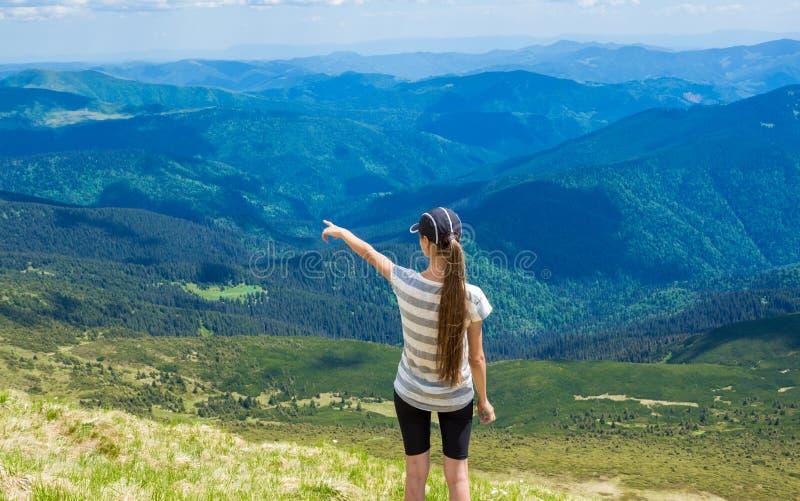 A mulher que caminha apontar ao céu aprecia a vista bonita na montanha imagens de stock royalty free