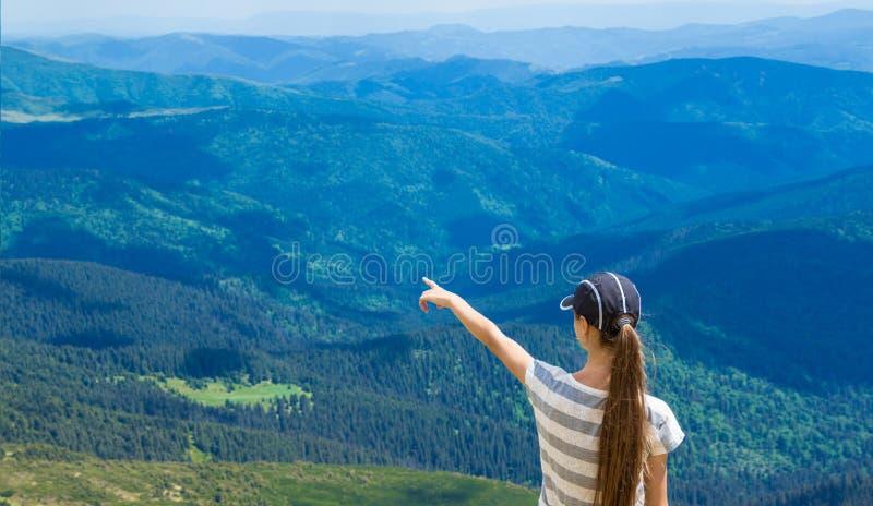 A mulher que caminha apontar ao céu aprecia a vista bonita na montanha foto de stock