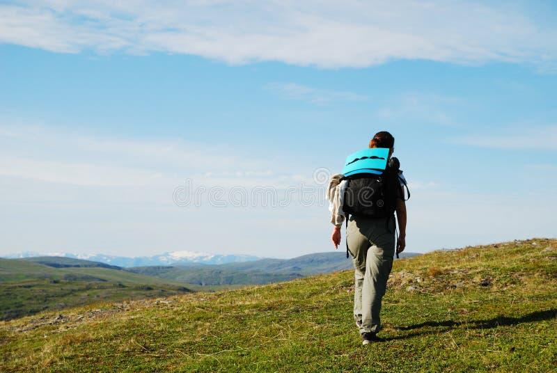 Mulher que caminha entre montes verdes e o céu azul. imagem de stock royalty free