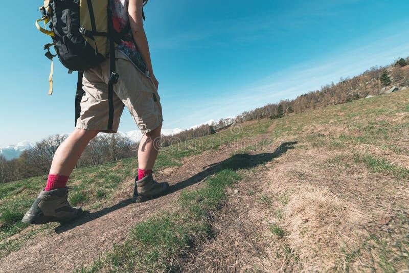 Mulher que caminha na montanha, ascendente próximo da parte do corpo, uma pessoa que anda nos cumes, curso backpacking da aventur fotos de stock