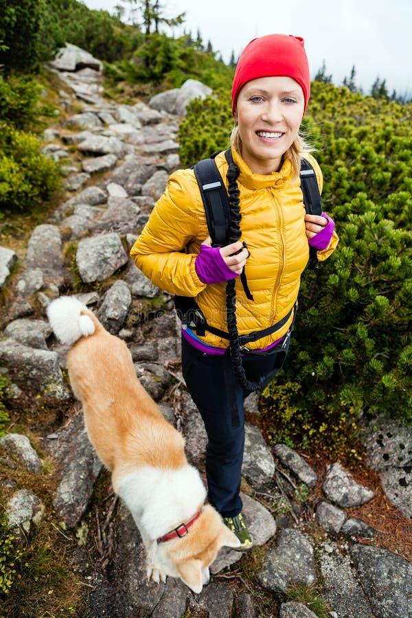 Mulher que caminha nas montanhas e no cão de passeio de akita imagens de stock royalty free