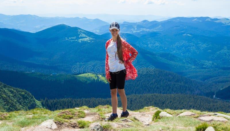 Mulher que caminha nas montanhas no dia ensolarado fotografia de stock royalty free