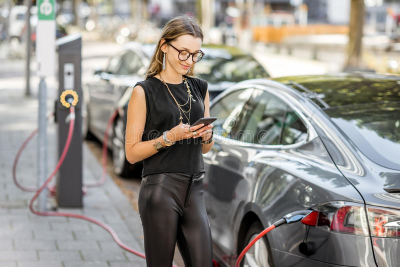 Mulher que carrega o carro bonde fora foto de stock royalty free