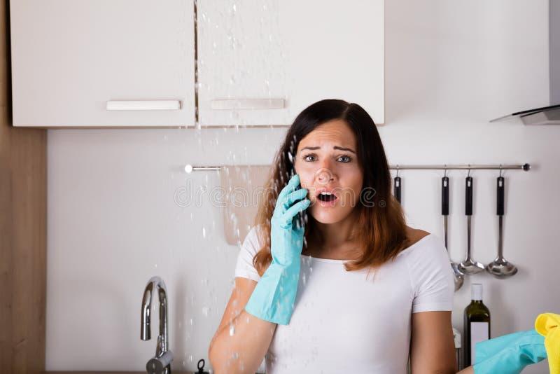 Mulher que chama ao problema de For Water Leakage do encanador imagens de stock royalty free