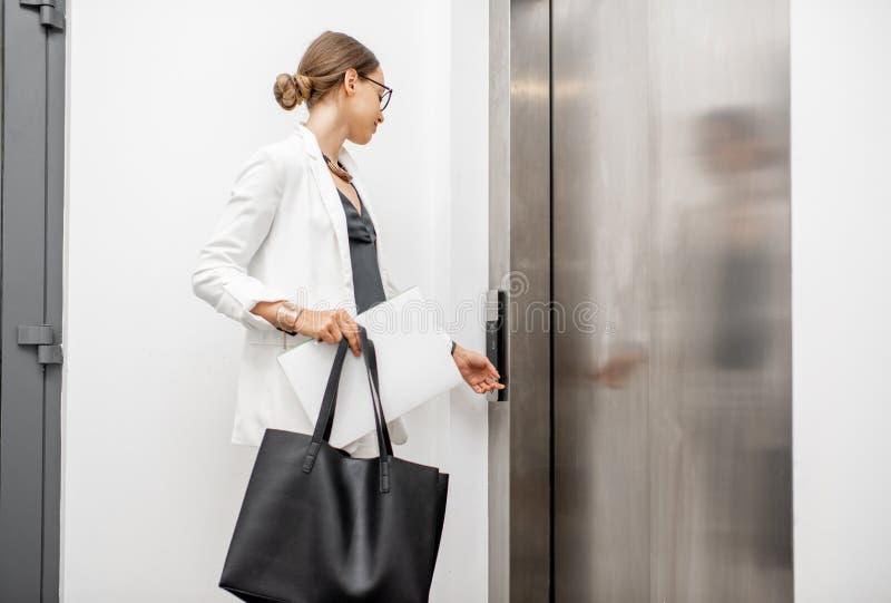 Mulher que chama o elevador foto de stock