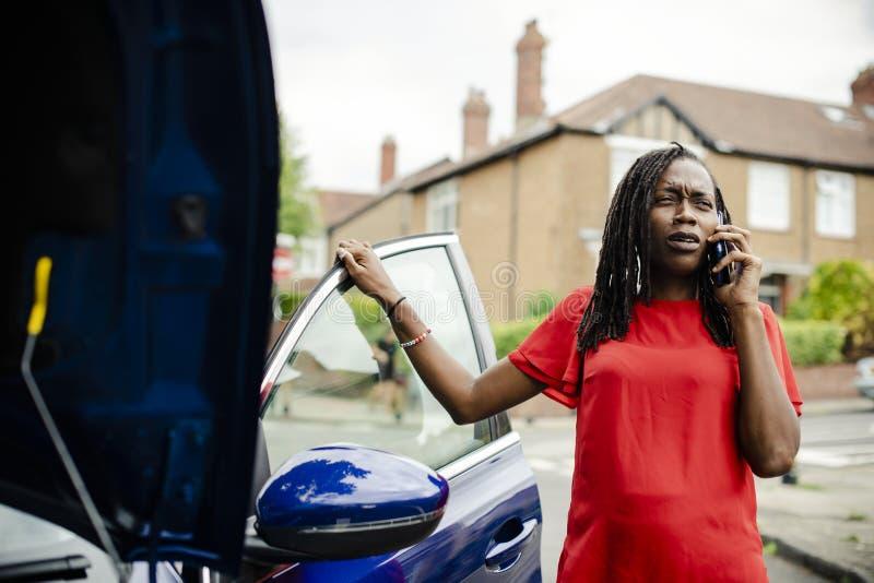 A mulher que chama para a ajuda como seu carro dividiu fotos de stock royalty free