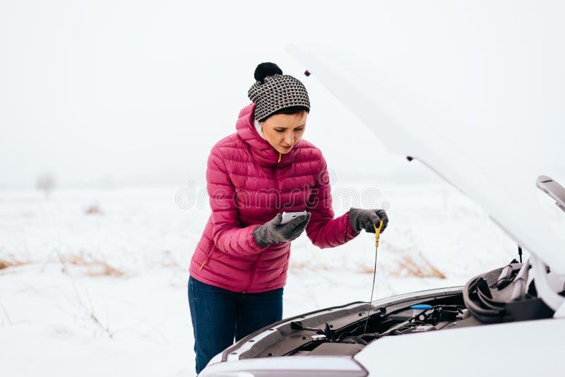 Mulher que chama para a ajuda ou o auxílio - divisão do carro do inverno foto de stock royalty free