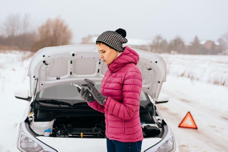 Mulher que chama para a ajuda ou o auxílio - divisão do carro do inverno imagens de stock
