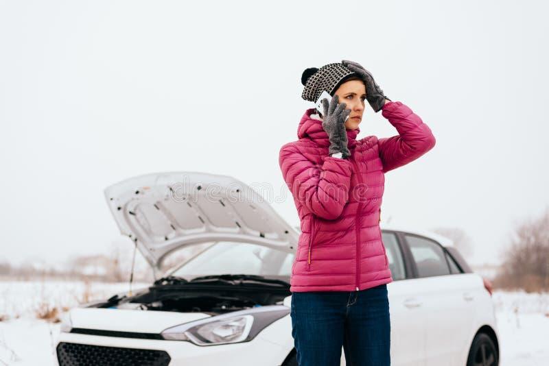 Mulher que chama para a ajuda ou o auxílio - divisão do carro do inverno imagens de stock royalty free