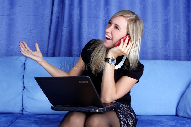 Mulher que chama pelo telefone e que trabalha com PC imagens de stock royalty free