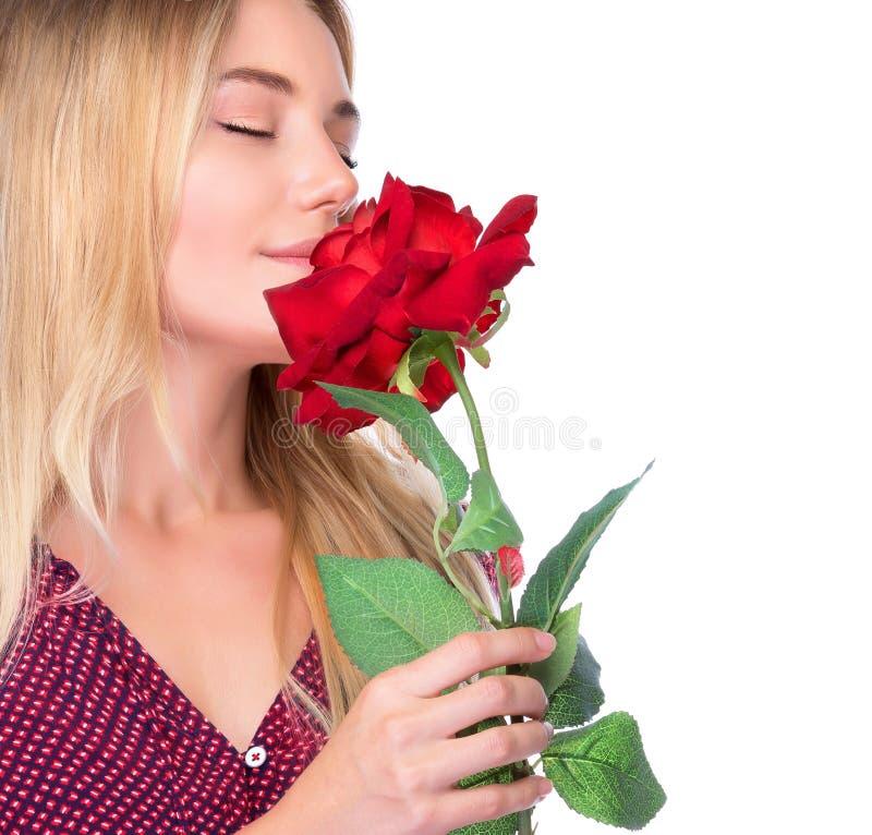 Mulher que cheira a rosa bonita do vermelho fotos de stock royalty free