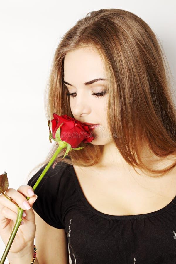 Mulher que cheira uma rosa vermelha imagem de stock royalty free