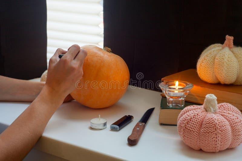 Mulher que cinzela a abóbora na tabela na casa Família que prepara-se para o feriado, processo de fazer a lanterna de Jack O para foto de stock
