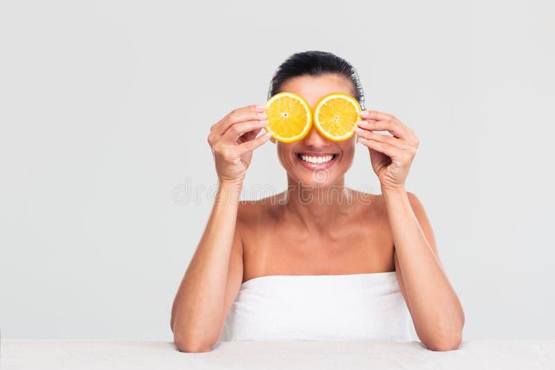 Mulher que cobre seus olhos com a laranja imagens de stock