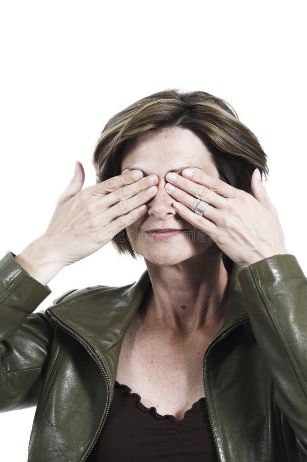 Mulher que cobre seus olhos com suas mãos fotos de stock royalty free