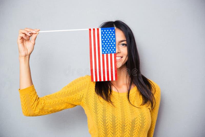 Mulher que cobre sua cara com a bandeira americana imagens de stock