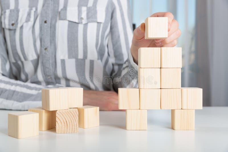 Mulher que coloca a última parte aos blocos de madeira na forma do foguete Comece acima o conceito do sucesso do lançamento do ne imagens de stock