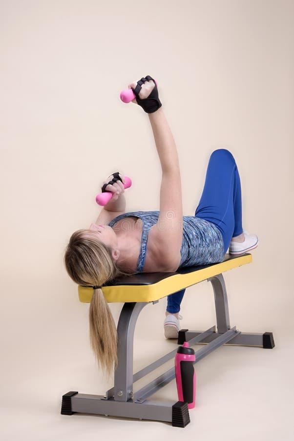 Mulher que coloca em um banco do treinamento do gym usando pesos imagens de stock royalty free