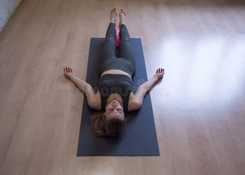 Mulher que coloca na esteira cinzenta na pose de relaxamento no assoalho, classe da ioga, vista dianteira fotos de stock