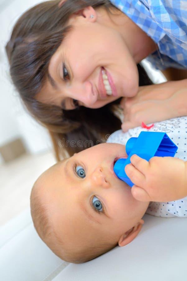 Mulher que coloca no assoalho com bebê foto de stock