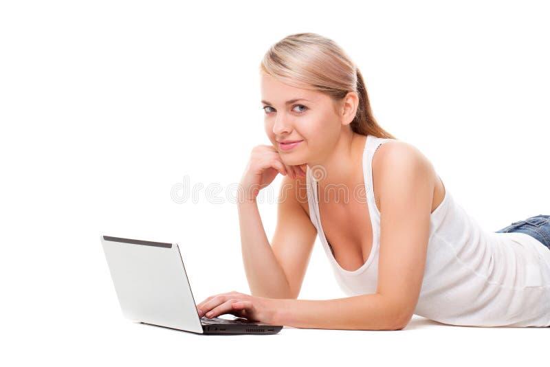 Mulher que coloca no assoalho com portátil imagem de stock