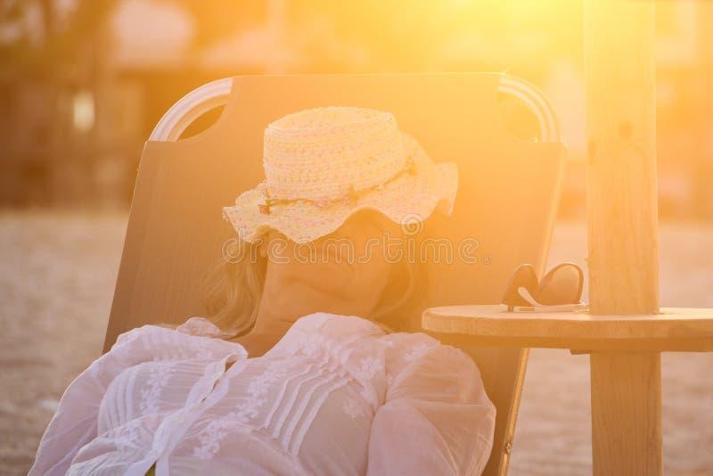 Mulher que coloca no Sunbed e que dorme na praia fotografia de stock royalty free